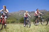 Teenage boys and girl biking — Stock Photo
