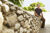 Tourist sitting on Stone Wall — Stock Photo