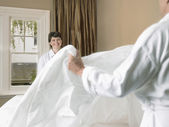 Smiling couple making bed together — Stock Photo