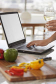 Man using lap top and chopping peppers — Stock Photo