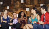 Group of friends talking in bar — Stock Photo