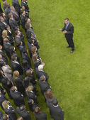 Business man facing large group of people — Stock Photo