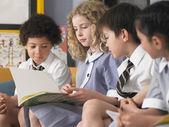 Школьникам чтение книги — Стоковое фото