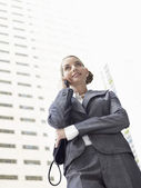 Low angle view of businesswoman conversing mobile phone against tall office building — Stock Photo