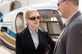 Businesspeople standing beside helicopter — Stock Photo