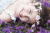 Girl with flower headdress lying in field — Stock Photo