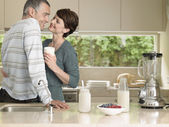 Smiling couple flirting in kitchen — Stock Photo