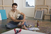 Male artist sitting with painting tools — Stock Photo