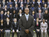 Business man standing in front of people — Stock Photo