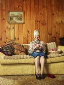 Senior woman on sofa knitting — Stock Photo