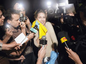 Woman with cleaning equipment surrounded by paparazzi — Stock Photo