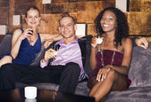 Man with women sitting on couch in bar — Stock Photo