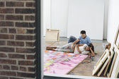 Couple reclining by painting on floor of studio — Stok fotoğraf