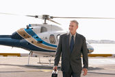 Businessman arriving on helicopter pad — Stock Photo