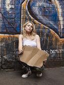 Woman squatting by brick wall — Stockfoto