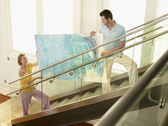 Couple moving painting up stairs — Stock Photo