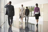 Businesspeople walking in office corridor — Stock Photo