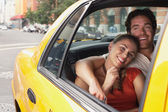 Couple in yellow taxi cab — Stock Photo