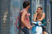 Woman on moped talking to man — Stock Photo