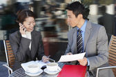 Businesspeople reviewing documents at cafe — Stock Photo