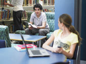 Girl looking at boy in library — Stock Photo