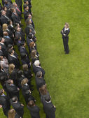 Business woman facing large group of people — Stock Photo