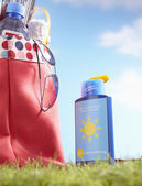 Bottle of suntan lotion and bag — Stock Photo