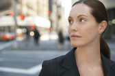 Businesswoman by intersection in street — Stock Photo