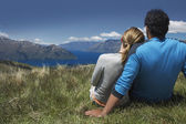 Couple cuddling looking over lake and hills — Stock Photo