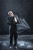 Businessman struggling to open umbrella — Stock Photo