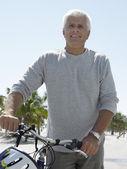 Homem com bicicleta na praia tropical — Foto Stock