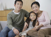 Couple and daughter Posing on Sofa — Stock Photo