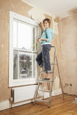 Woman standing on step ladder — Stock Photo