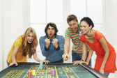 Friends celebrating win on roulette table — Stock Photo