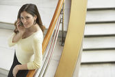 Woman leaning on railing of staircase — Stock Photo