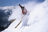 Skier skiing through powdery snow — Stock Photo