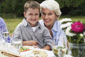 Grandmother with grandson on lap in garden — Stock Photo