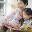 Mother sitting with daughter reading a book — Stock Photo