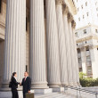 Stock Photo: Attorneys shaking hands on courthouse steps