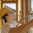 Stock Photo: Construction worker working on building window