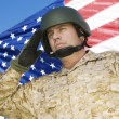 Soldier saluting in front of flag — Stock Photo #33832411