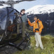 Hikers climbing out of helicopter — Stock Photo