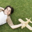 Boy lying in grass with toy airplane — Stock Photo