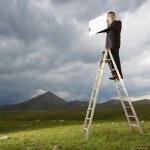 Бизнесмен, стоя на лестнице — Стоковое фото