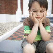 Sad boy sitting on steps — Stock Photo