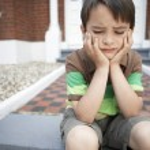 Sad boy sitting on steps — Stock Photo #33834005