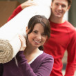 Couple Carrying Rolled Carpet — Stock Photo #33834085