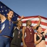 Athletes holding American flag — Stock Photo #33834441