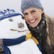 Woman embracing snowman — Stock Photo #33835001