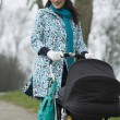 Mother pushing stroller in park — Stock Photo #33835107